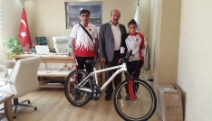 Milli takıma seçilen atlete bisiklet hediye edildi