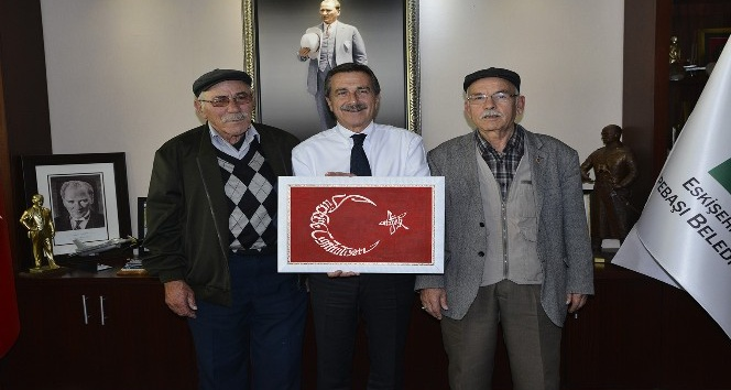 Oğlunun özel olarak yaptığı el işlemesi Türk Bayrağı'nı Başkan Ataç'a hediye etti